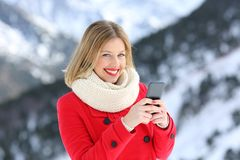 Happy woman posing holding a phone in winter holiday royalty free stock photography