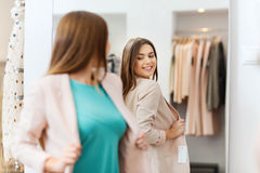 Happy woman posing at mirror in clothing store royalty free stock photography