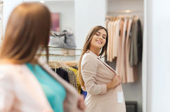 Happy woman posing at mirror in clothing store stock images