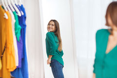 Happy woman posing at mirror in home wardrobe. Clothing, fashion, style and people concept - happy woman choosing clothes and posing at mirror at home wardrobe Stock Photo