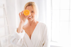 Happy woman posing with piece of orange. Express positivity. Positive girl keeping smile on her face and covering her right eye while looking straight at camera royalty free stock images