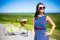 Happy woman posing on the road with retro bicycle Royalty Free Stock Photography