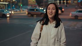 Happy woman posing in the street in front of blurred city traffic lights in the night, retro color toned stock footage