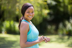 Happy woman posing and touching her watch Stock Images
