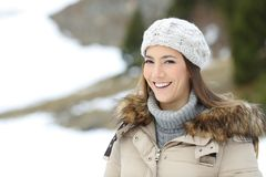 Happy woman posing on winter holiday. Happy woman posing looking at camera on winter holiday in a snowy mountain stock photo