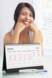 Happy woman with positive pregnancy test. And calendar. A concept being success to get pregnant Royalty Free Stock Photography
