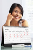 Happy woman with positive pregnancy test. And calendar. A concept being success to get pregnant Royalty Free Stock Photos