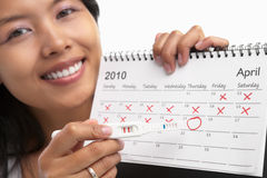 Happy woman, positive pregnancy test & calendar. Happy woman with positive pregnancy test and calendar. A concept being success to get pregnant Royalty Free Stock Image