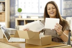 Happy woman with postal packet. Young woman unpacking postal packet, smiling happy Royalty Free Stock Photos