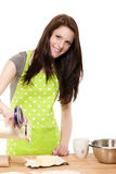 Happy woman pouring baking flour on a table. Happy baking woman pouring baking flour on a table on white background Royalty Free Stock Image