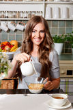 Happy woman pouring milk to cornflakes Stock Photos