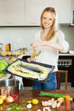 Happy woman pouring oil into fish Stock Image