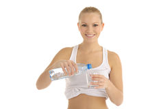 Happy woman pours water into a glass Royalty Free Stock Photo