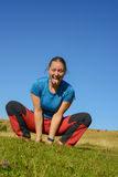 Happy woman is practicing yoga in mountains autumn. Pose of the lion  on the background of blue sky. Cheerful hiker woman is having fun in outdoors Royalty Free Stock Images