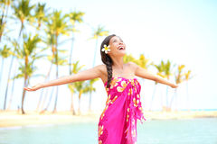 Happy woman praising freedom, palm beach in sarong. Happy woman praising freedom smiling on hawaiian palm beach in sarong, arms stretched out. Beautiful mixed Royalty Free Stock Images