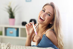Happy woman with pregnancy test at home. Picture showing happy woman with pregnancy test at home stock photography