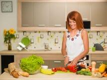 Happy woman preparig a salad royalty free stock photo