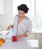 Happy woman preparing a cup of coffee wearing pajamas Royalty Free Stock Photography