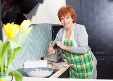 Happy woman preparing pasta with cheese Royalty Free Stock Photography