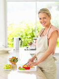 Happy woman preparing salad in the kitchen Royalty Free Stock Image