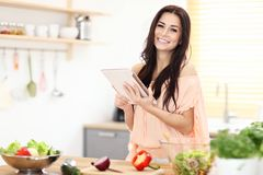 Happy woman preparing salad in modern kitchen and holding tablet. Picture of happy woman with vegetables in modern kitchen Stock Images
