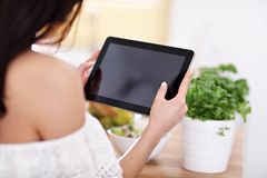 Happy woman preparing salad in modern kitchen and holding tablet. Picture of happy woman with vegetables in modern kitchen Royalty Free Stock Photo