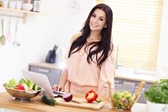 Happy woman preparing salad in modern kitchen. Picture of happy woman with vegetables in modern kitchen Royalty Free Stock Images