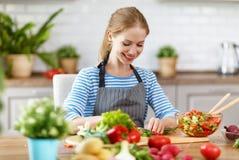 Happy woman preparing vegetable salad in kitchen Stock Image