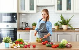 Happy woman preparing vegetable salad in kitchen stock photos