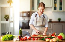 Happy woman preparing vegetable salad in kitchen stock images