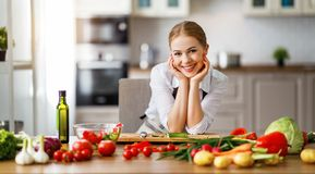 Happy woman preparing vegetable salad in kitchen royalty free stock photo