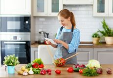 Happy woman preparing vegetables in kitchen on prescription with royalty free stock photography
