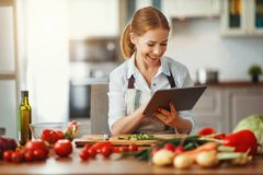 Happy woman preparing vegetables in kitchen on prescription with tablet royalty free stock image