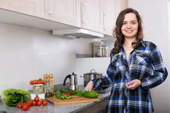 Happy woman preparing veggies at home. Happy brunette girl  in casual preparing veggies at home  kitchen Stock Photography