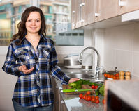 Happy woman preparing veggies at home. Happy young woman preparing veggies and smiling at home Stock Image