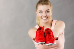 Happy woman presenting sportswear trainers shoes. Happy sporty smiling woman presenting sportswear trainers red shoes, comfortable footwear perfect for workout Royalty Free Stock Image