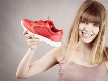 Happy woman presenting sportswear trainers shoes. Happy sporty smiling woman presenting sportswear trainers red shoes, comfortable footwear perfect for workout Stock Photography