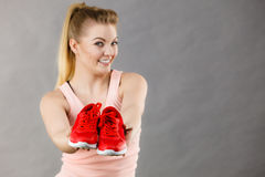 Happy woman presenting sportswear trainers shoes Stock Images