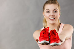 Happy woman presenting sportswear trainers shoes. Happy sporty smiling woman presenting sportswear trainers red shoes, comfortable footwear perfect for workout Royalty Free Stock Photos