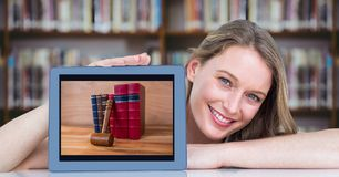 Happy woman presenting tablet with pile of books while sitting at desk in library Stock Photo