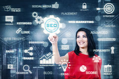 Happy woman presses SEO button Stock Images