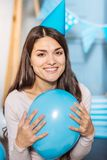 Happy woman pressing balloon to her chest and smiling Royalty Free Stock Images