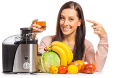 Happy woman is pressing the juice from the fruit Stock Image