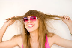 Happy woman pulling hair. Portrait of a happy, laughing young woman  pulling her long hair.  White background Stock Photo