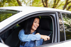 Happy woman pulling on seatbelt inside white car Stock Photography