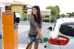 Happy woman pumping gas in car Royalty Free Stock Photos