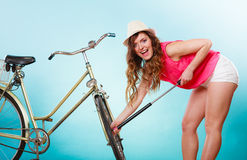 Happy woman pumping up tire tyre with bike pump. Royalty Free Stock Image