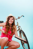 Happy woman pumping up tire tyre with bike pump. Stock Photo