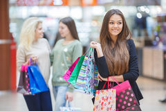 Happy woman with purchases on a background of friends Royalty Free Stock Photography