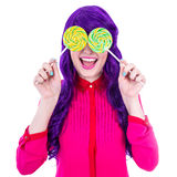 Happy woman with purple hair covering her eyes with lollipops is Stock Images